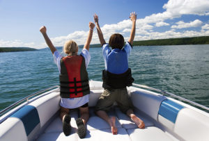 """Two kids in the bow of a motorboat acting out a scene from the movie """"Titanic""""."""